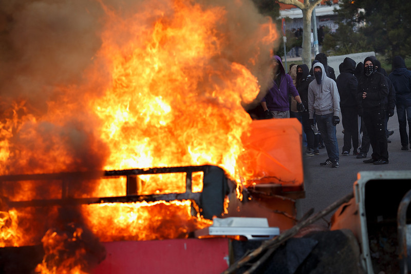 . Protesters stand behind a burning barricade during a protest against the government\'s education reforms and cutbacks in university grants and staffing in Campus Ciudad Universitaria on March 26, 2014 in Madrid, Spain. The students began occupying a campus building at Ciudad Universitaria several days ago in protest against the governments\' cuts. Today, they were removed from the premises by police, who made fifty arrests, after the University requested their assistance.  (Photo by Pablo Blazquez Dominguez/Getty Images)