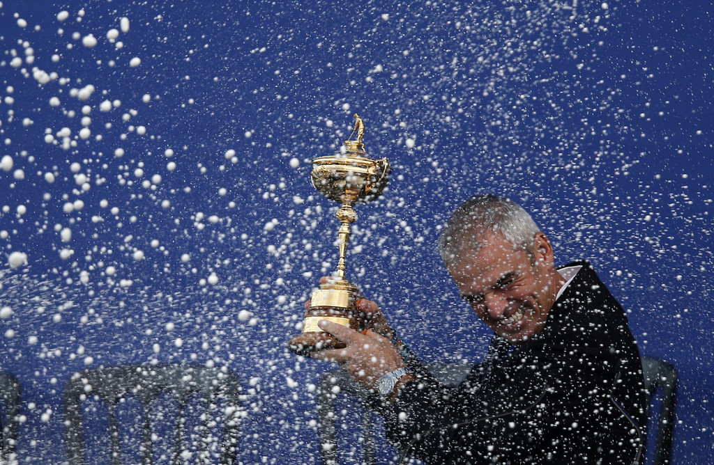 . Captain of Team Europe Paul McGinley of Ireland is sprayed with champagne as he holds the Ryder Cup trophy on the final day of the Ryder Cup golf tournament at the Gleneagles Hotel in Gleneagles, Scotland, on September 28, 2014. Jamie Donaldson grabbed the crucial point Paul McGinley\'s side needed for the win when he defeated Keegan Bradley 4 and 3 in the 10th of the closing 12 singles. AFP PHOTO/ADRIAN DENNIS