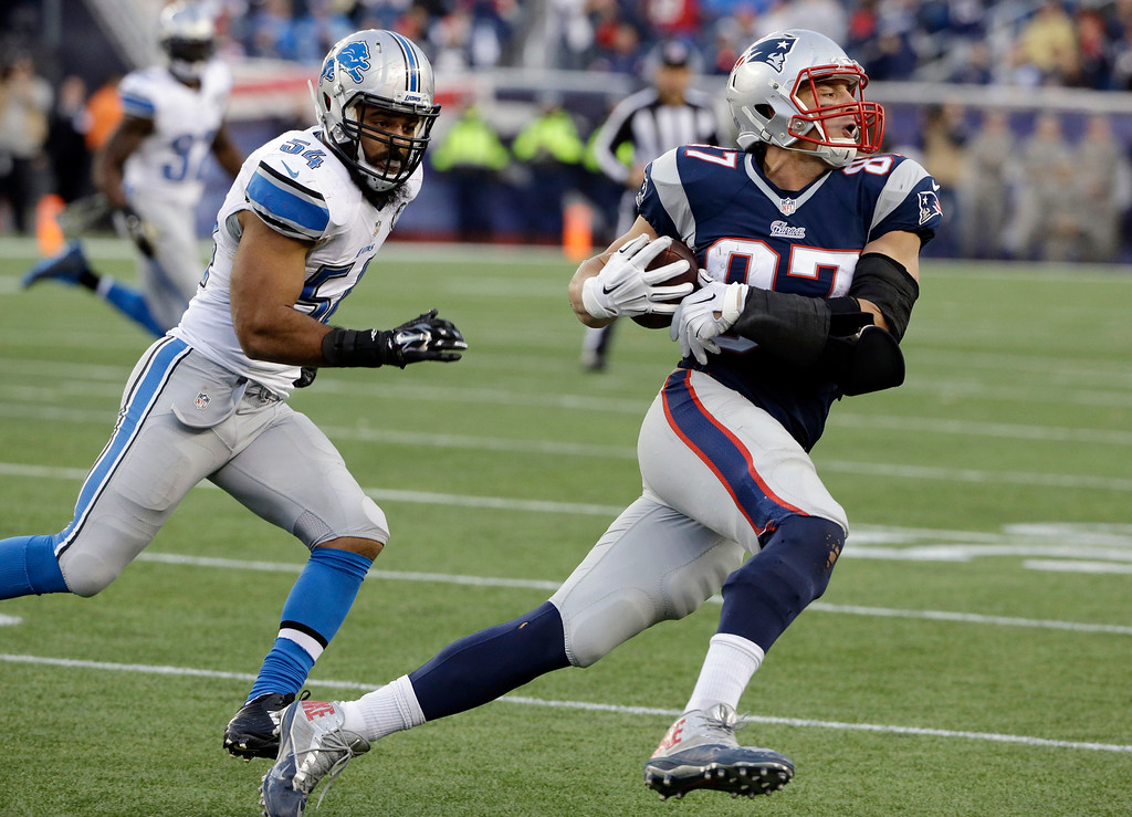 . New England Patriots tight end Rob Gronkowski (87) runs from Detroit Lions outside linebacker DeAndre Levy (54) after catching a pass in the second half of an NFL football game Sunday, Nov. 23, 2014, in Foxborough, Mass. (AP Photo/Stephan Savoia)