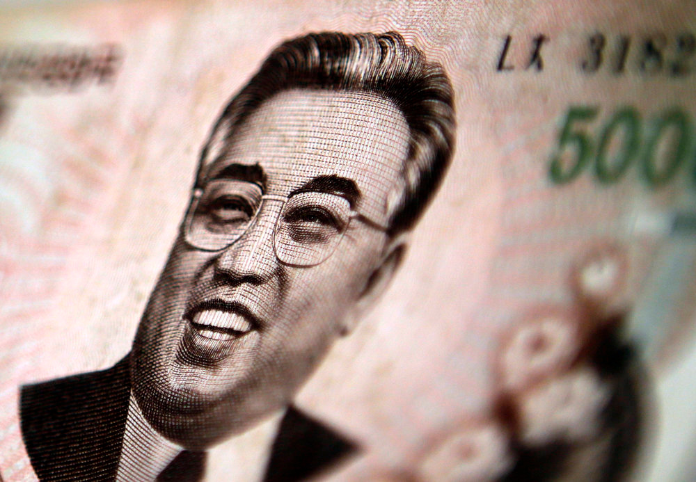 . North Korean leader Kim Il-sung is seen on this 5000 North Korea won banknote in this photo illustration taken in Shanghai May 23, 2013. Chinese currency and U.S. dollars are being used more widely than ever in North Korea instead of the country\'s own money. The use of dollars and Chinese yuan, or renminbi, has accelerated since a revaluation of the North Korean won in 2009 wiped out the savings of millions of people, said experts on the country, defectors and Chinese border traders. The black market exchange rate for this 5000 North Korean won banknote is equivalent to $0.65, while the official North Korean exchange rate stands at more than $65.  REUTERS/Carlos Barria