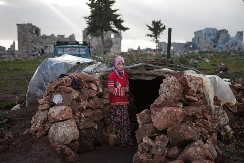 Description of . A Syria girl stands at the entrance of a makeshift home set up in the catacombs of the ruins of an ancient building in the ancient Roman city of of Serjilla, in northwestern Syria, on February 11, 2013, after fleeing the fighting between rebel forces and pro-government troops in the town of Kfar Nubul,  in the northwestern province of Idlib. DANIEL LEAL-OLIVAS/AFP/Getty Images