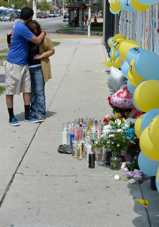 . Andrew and his mother Ruth Escalera are emotional as they look at the memorial. Andrew graduated last year from the rival high school, South El Monte H.S. Students at El Monte High School brought flowers, candles and other items in remembering Adrian Castro, a Senior student who was killed in bus crash in Northern California that took the lives of 10 people. El Monte, CA. 4/13/2014(Photo by John McCoy / Los Angeles Daily News)