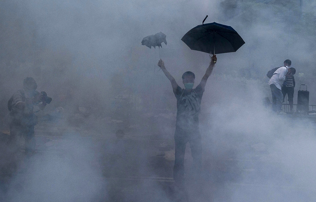 . A pro-democracy demonstrator gestures after police fired tear gas towards protesters near the Hong Kong government headquarters on September 28, 2014. Police fired tear gas as tens of thousands of pro-democracy demonstrators brought parts of central Hong Kong to a standstill on September 28, in a dramatic escalation of protests that have gripped the semi-autonomous Chinese city for days. AFP PHOTO / XAUME  OLLEROS/AFP/Getty Images