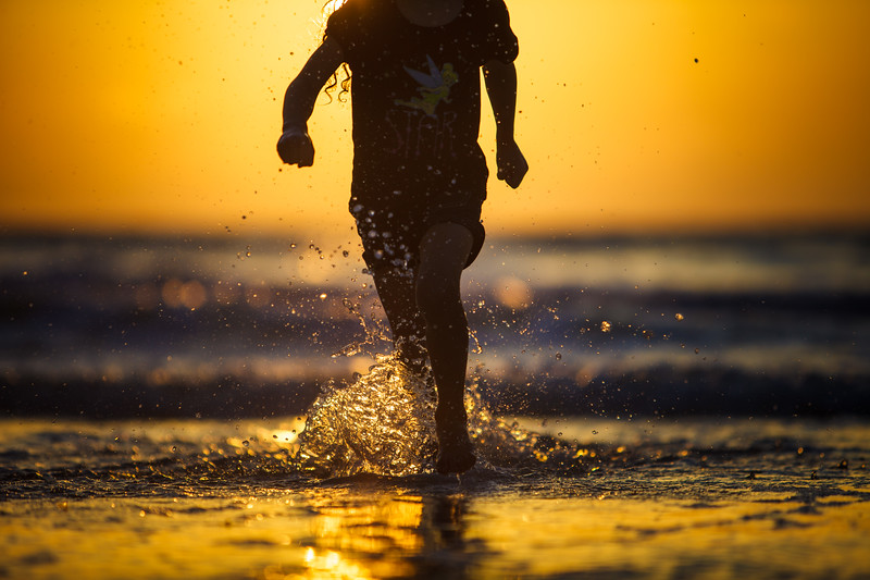 Young girl running on the ocean shore.