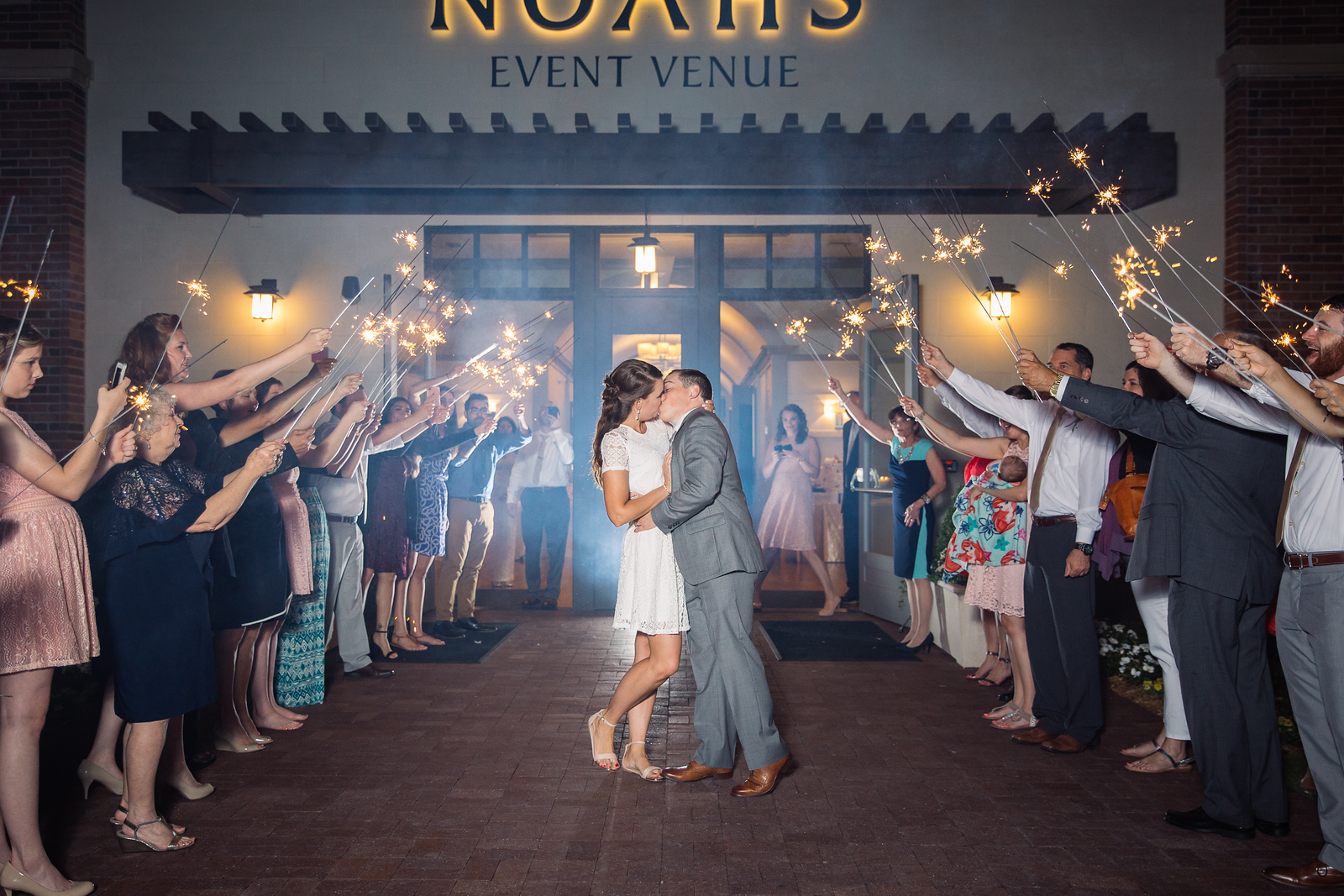 Bride and groom share a kiss at their sparkler send off