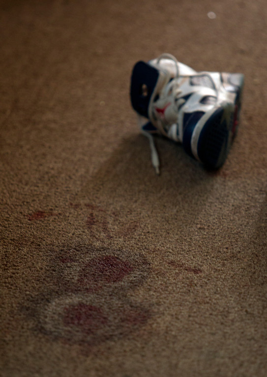 . Blood stains the carpet inside an apartment at the scene of a homicide in the 3400 block of Wilson Avenue in Oakland, Calif., Thursday, July 18, 2013. An 8-year-old girl was killed when an unknown assailant came to the door of an apartment around 11:15 p.m. Wednesday night and fired multiple shots. Three other people were injured. (D. Ross Cameron/Bay Area News Group)