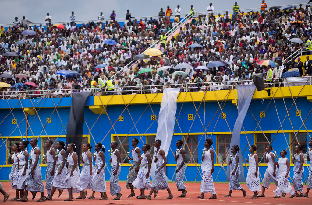 . Performers re-enacting some of the events enter a public ceremony to mark the 20th anniversary of the Rwandan genocide, at Amahoro stadium in Kigali, Rwanda Monday, April 7, 2014.  (AP Photo/Ben Curtis)