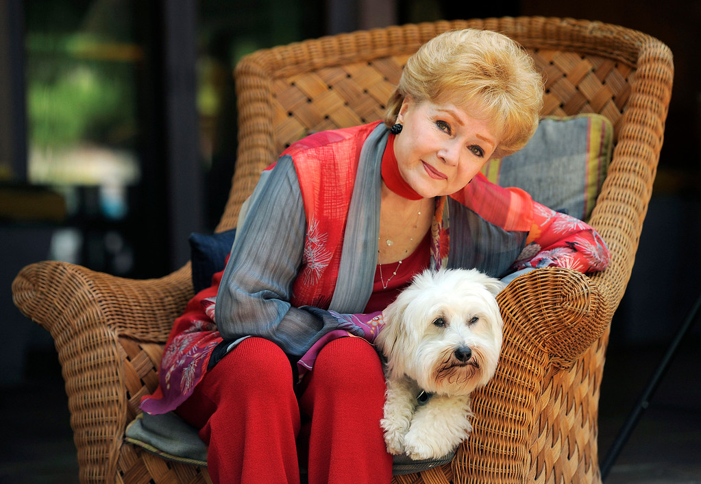 """. In this Tuesday, May 21, 2013 photo, Debbie Reynolds, a cast member in the film \""""Behind the Candelabra,\"""" poses for a portrait with her dog, Dwight, in Beverly Hills, Calif. Reynolds plays Frances, the mother of the pianist and vocalist, Liberace. HBO debuts �Behind the Candelabra� in the US, Sunday, May 26, 2013. (Photo by Chris Pizzello/Invision/AP)"""