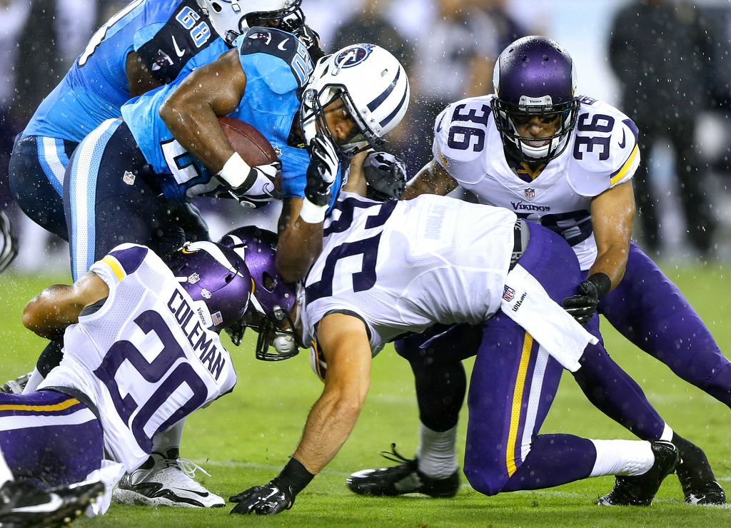 . Tennessee Titans running back Bishop Sankey is stopped by Minnesota Vikings defenders Kurt Coleman (20), Mike Zimmer (59) and Robert Blanton (36) in the first quarter. (AP Photo/Wade Payne)