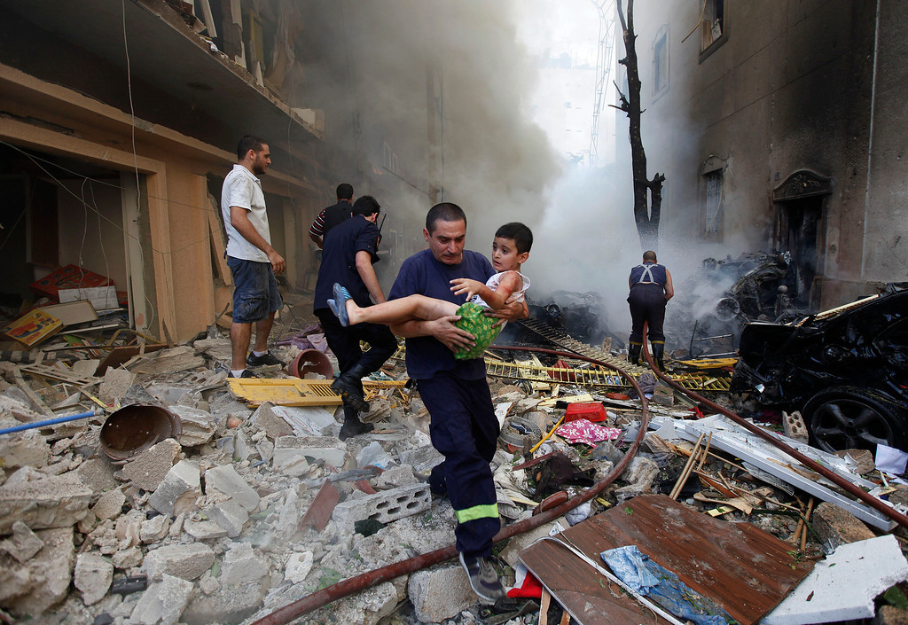 . In this Oct. 19, 2012 file photo, a Lebanese rescue man, carries an injured boy at the scene of an explosion in the mostly Christian neighborhood of Achrafiyeh, Beirut, Lebanon. A car bomb ripped through eastern Beirut, shearing the balconies of off residential buildings and sending bloodied victims pouring out into the streets in the most serious blast this city has seen in years. (AP Photo/Hussein Malla, File)