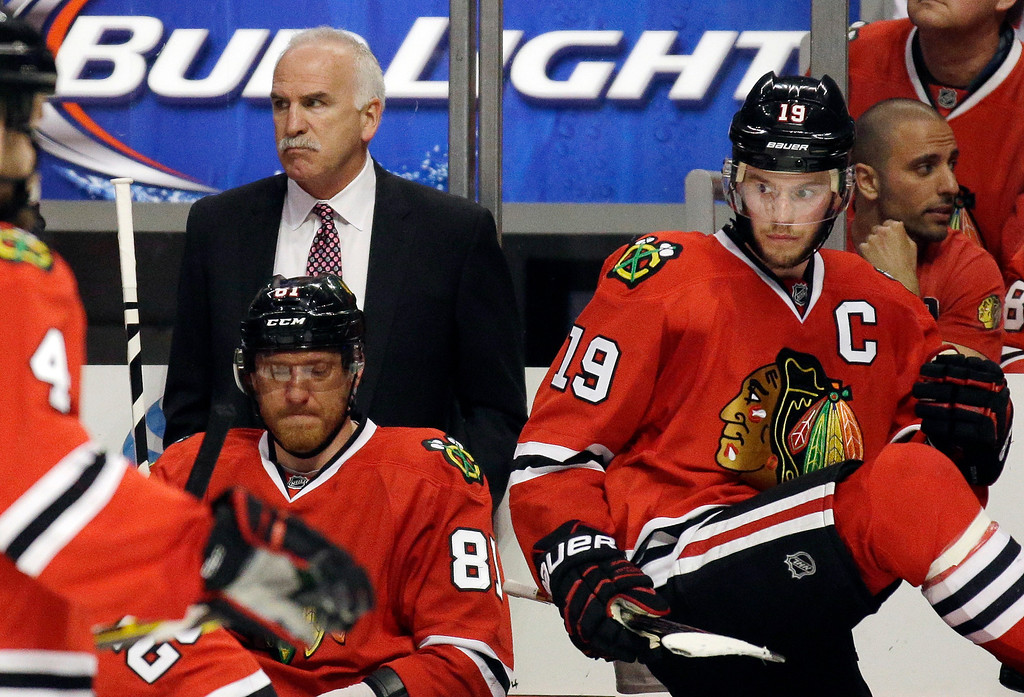 . Chicago Blackhawks head coach Joel Quenneville watches as Chicago Blackhawks center Jonathan Toews, right, is ready to take the ice during the first period in Game 7 of the Western Conference finals in the NHL hockey Stanley Cup playoffs against the Los Angeles Kings Sunday, June 1, 2014, in Chicago. (AP Photo/Nam Y. Huh)