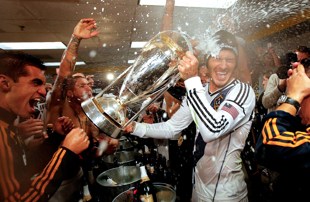 . In this Dec. 1, 2012 file photo, Los Angeles Galaxy\'s David Beckham, center, of England, is sprayed with champagne as they celebrate in the dressing room after defeating the Houston Dynamo 3-1 in the MLS Cup championship soccer game in Carson, Calif.  (AP Photo/Jae C. Hong, File)