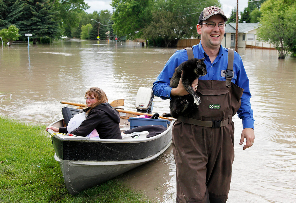 . Roger Poirier, holds his family\'s cat, Smartie, as his wife Crystal looks on after rescuing it from their flooded house in High River, Alta., Thursday, June 20, 2013. Calgary city officials say as many as 100,000 people could be forced from their homes due to heavy flooding in western Canada, while mudslides have forced the closure of the Trans-Canada Highway around the mountain resort towns of Banff and Canmore. (AP Photo/The Canadian Press, Jeff McIntosh )