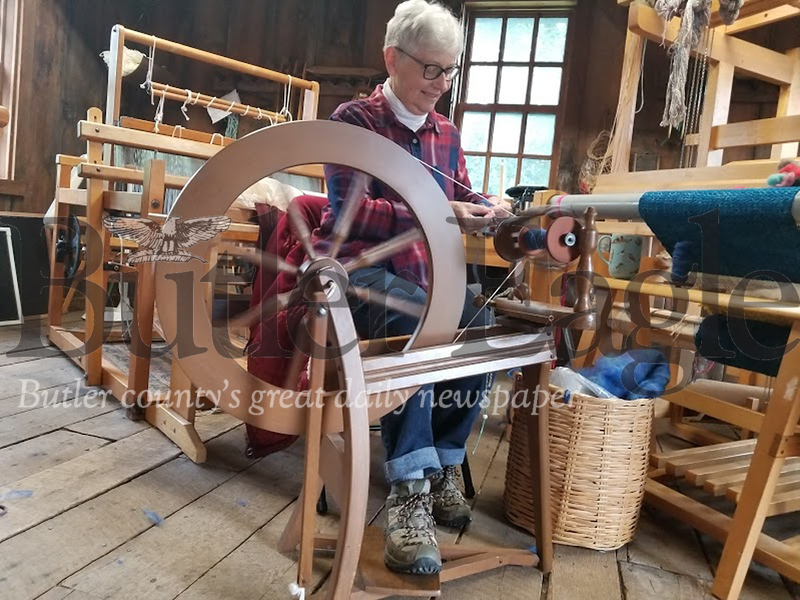 Windy Kovach, a member of the Harmony Museum and a volunteer at the Weaver Cabin, spins yarn in the antique cabin for the fall festival in Harmony.