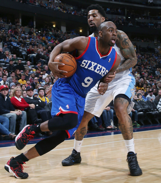 . Philadelphia 76ers guard James Anderson, front, drives for shot past Denver Nuggets forward Wilson Chandler during the first quarter of an NBA basketball game in Denver on Wednesday, Jan. 1, 2014. (AP Photo/David Zalubowski)