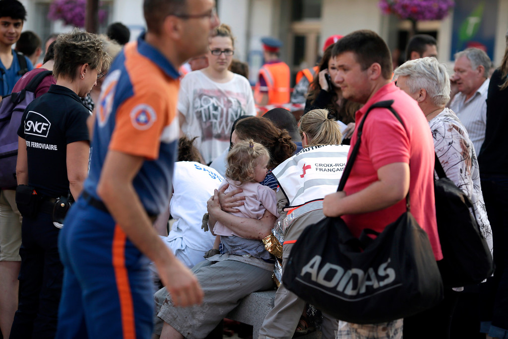 . A woman holds a child amidst rail workers and Red Cross workers on the site of a train accident in the railway station of Bretigny-sur-Orge, Friday, July 12, 2013 near Paris. (AP Photo/Kenzo Tribouillard, POOL)