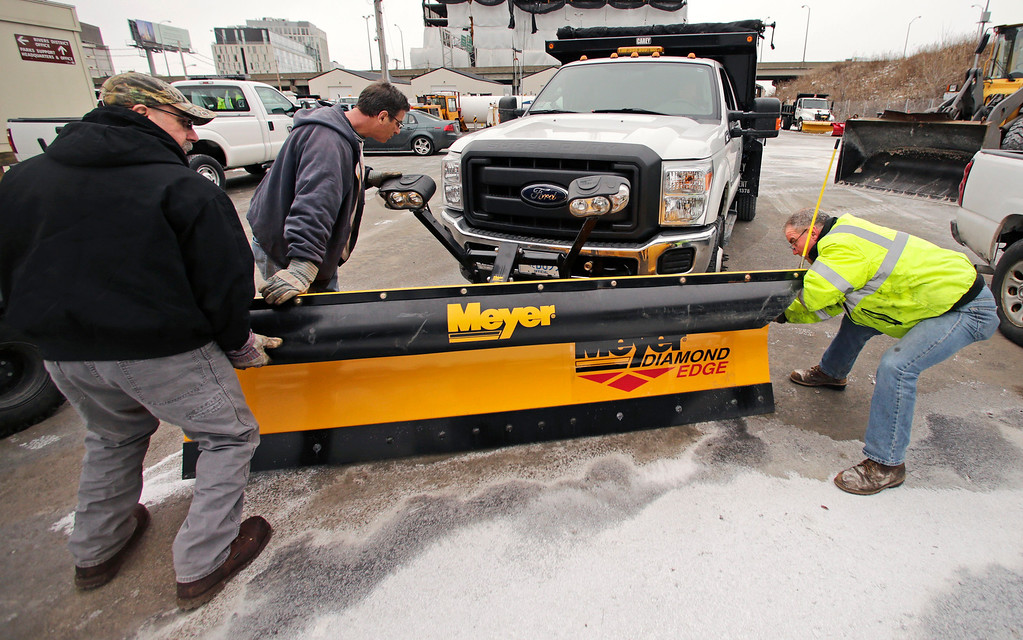 . Workers from the Mass. Dept. of Conservation and Recreation put a plow on a truck in advance of an expected winter snow storm Tuesday, Jan. 21, 2014, in Cambridge, Mass.  The Boston area is expected to get about a foot of snow by Wednesday evening. (AP Photo/Charles Krupa)