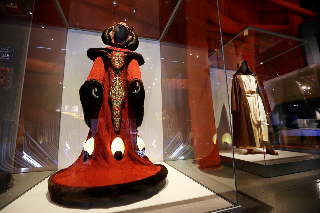 . In this photo taken Thursday, Jan. 29, 2015, Queen Amidala\'s throne room gown, left, and Obi-Wan Kenobi\'s costume are displayed as part of an exhibit on the costumes of Star Wars at Seattle�s EMP Museum. The creators of the new exhibit, with 60 original costumes from the six Star Wars movies, are hoping to gather geeks, fashionistas and movie fans together to discuss how clothing helps set the scene. The exhibit, �Rebel, Jedi, Princess, Queen: Star Wars and the Power of Costume,� will be in Seattle through early October and then travel across the United States through 2020. (AP Photo/Elaine Thompson)