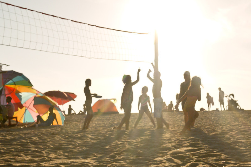 Group of kids playing beach volleyball.