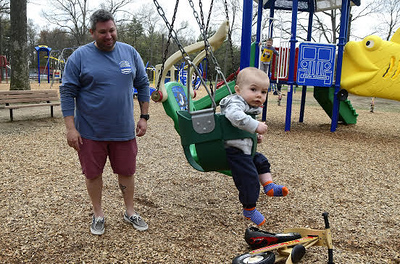 4/27/2017 Mike Orazzi   StaffMichael Nolan and his son Conor, 9 months, while enjoying the recently renovated playground in Plainville's Norton Park Thursday.