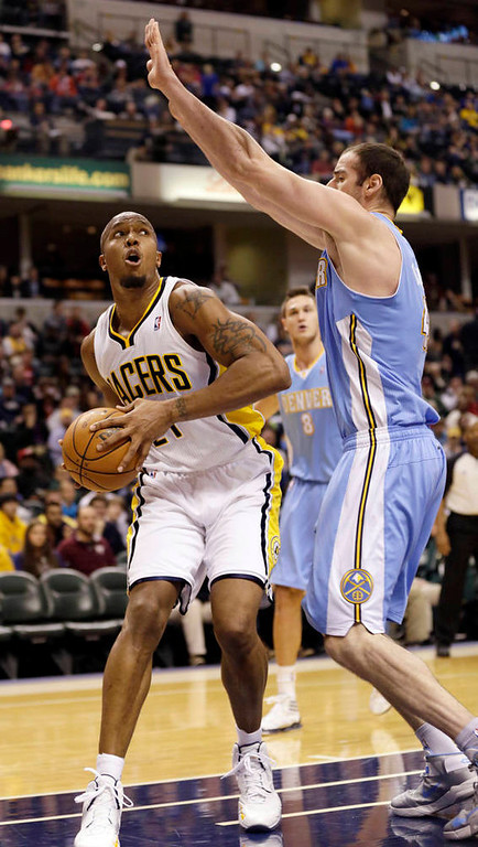 . Indiana Pacers forward David West, left, looks to shoot around the defense of Denver Nuggets center Kosta Koufos during the second half of an NBA basketball game in Indianapolis, Friday, Dec. 7, 2012. The Nuggets won 92-89. (AP Photo/AJ Mast)