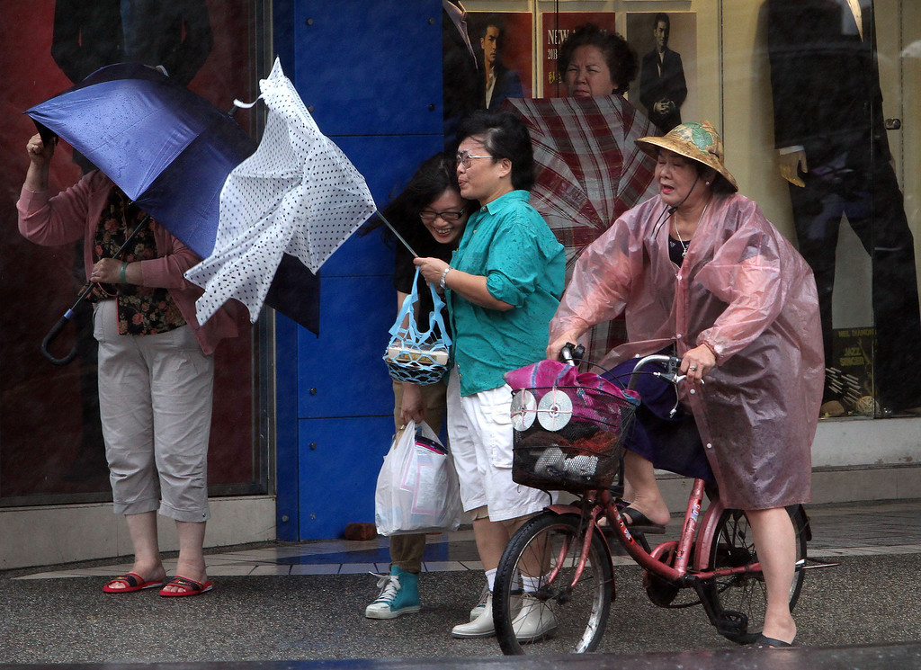 . Taiwanese women hold their umbrellas against powerful gusts of wind as Typhoon Fitow approaches in Taipei, Taiwan, Sunday, Oct. 6, 2013. (AP Photo/Chiang Ying-ying)