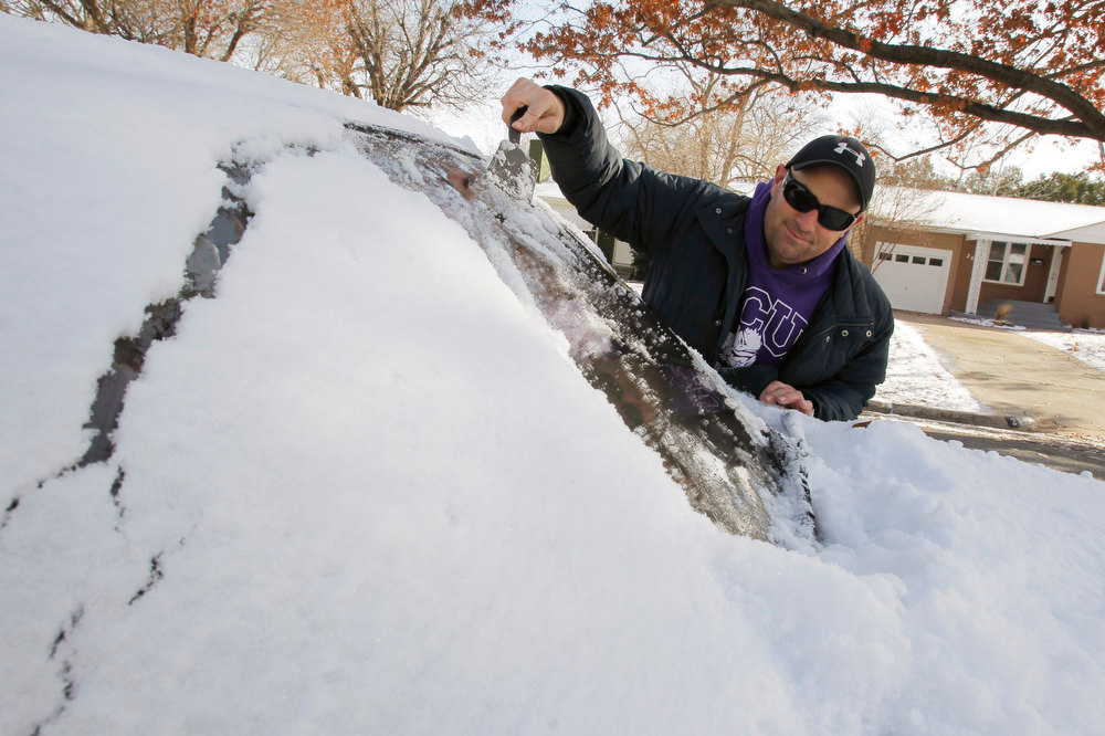 Description of . Nathan Elkins cleans his windshield of snow so he can go to work, Wednesday, Dec. 26, 2012, after winter weather covered the area with layer of snow on Christmas Day. (AP Photo/The Fort Worth Star-Telegram, Rodger Mallison)