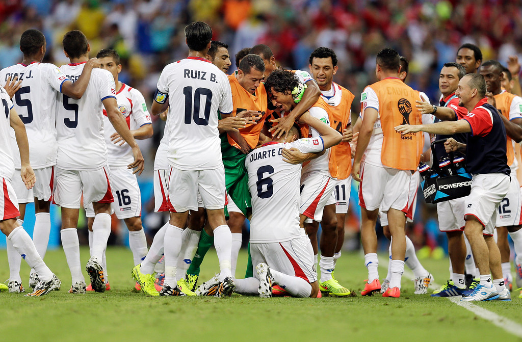 . Costa Rican players swarm over Costa Rica\'s Oscar Duarte (6) after he scored his side\'s second goal during the group D World Cup soccer match between Uruguay and Costa Rica at the Arena Castelao in Fortaleza, Brazil, Saturday, June 14, 2014.  (AP Photo/Natacha Pisarenko)