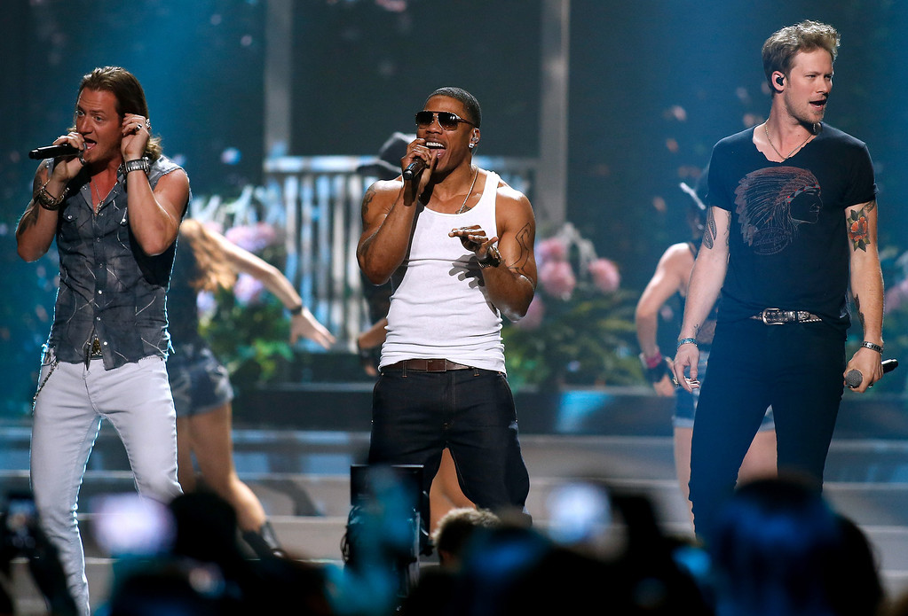 . Tyler Hubbard, left, and Brian Kelley, right, of Florida Georgia Line perform with Nelly, center, during the Miss USA 2014 pageant in Baton Rouge, La., Sunday, June 8, 2014. (AP Photo/Jonathan Bachman)