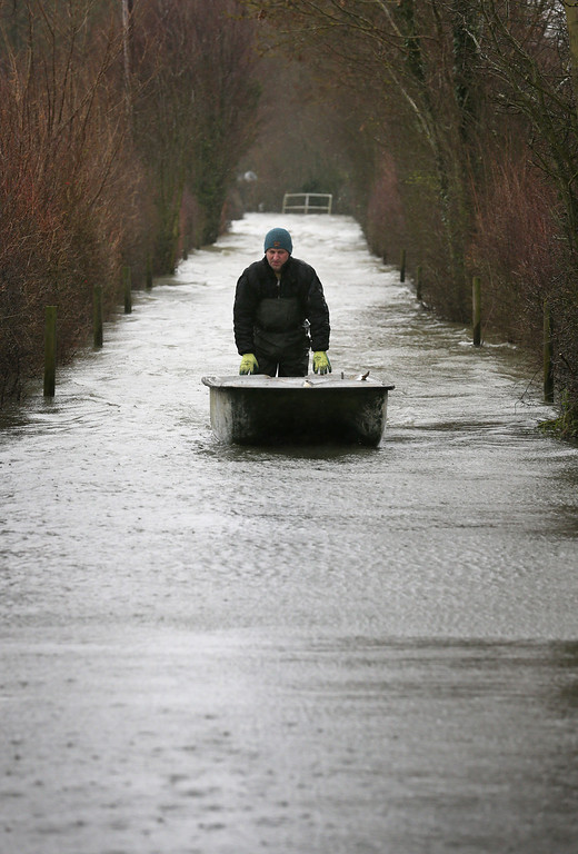 . James Georgiadis pushes his boat along a flooded lane to his house on February 12, 2014 in Wraysbury, England.The Environment Agency contiues to issue severe flood warnings for a number of areas on the river Thames in the commuter belt west of London. With heavier rains forecast for the coming week people are preparing for for the water levels to rise.  (Photo by Peter Macdiarmid/Getty Images)