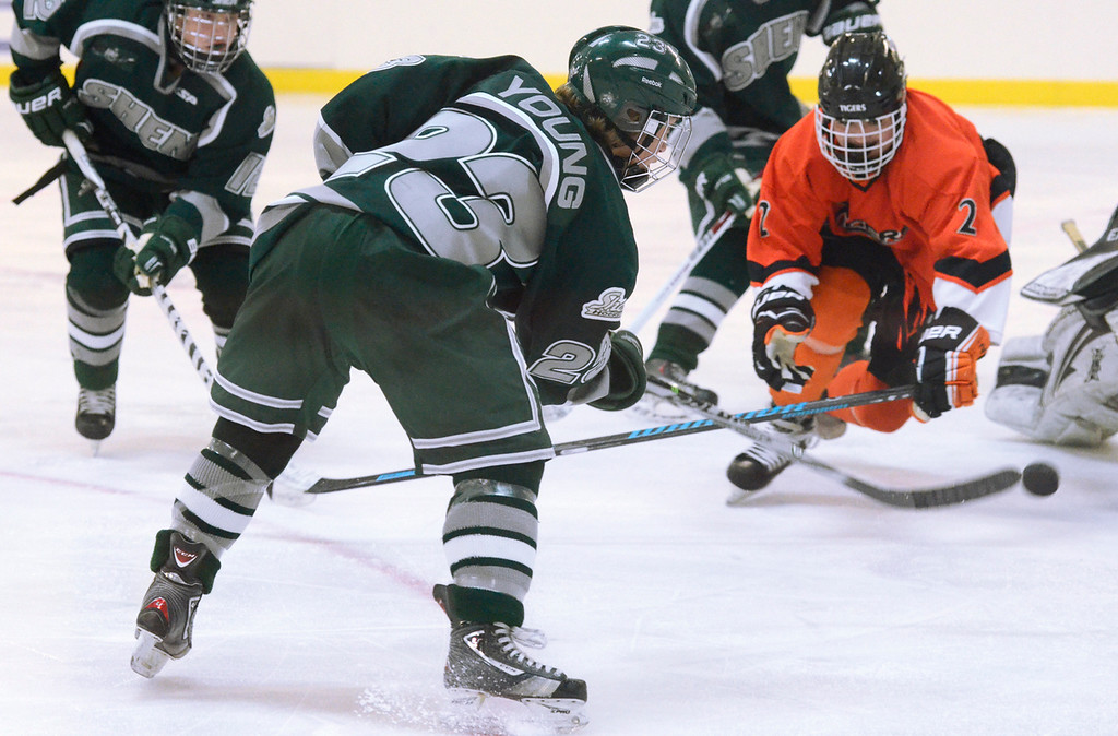 . Ed Burke - The Saratogian 12/07/13 Shen\'s Nick Young shoots on goal as Mamaroneck defenseman Cooper Lavan closes in during Saturday\'s action in the Don Kauth Memorial Tournament at Saratoga Springs Ice Rink.