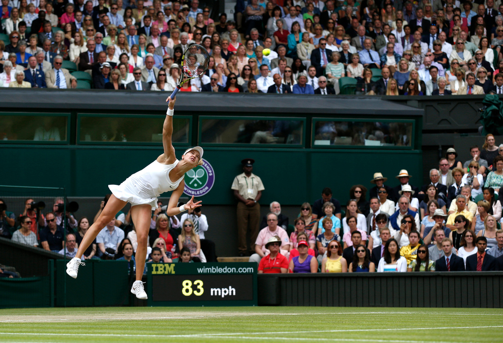 Description of . Eugenie Bouchard of Canada serves to Petra Kvitova of the Czech Republic during the women's singles final at the All England Lawn Tennis Championships in Wimbledon, London, Saturday, July 5, 2014. (AP Photo/Sang Tan)
