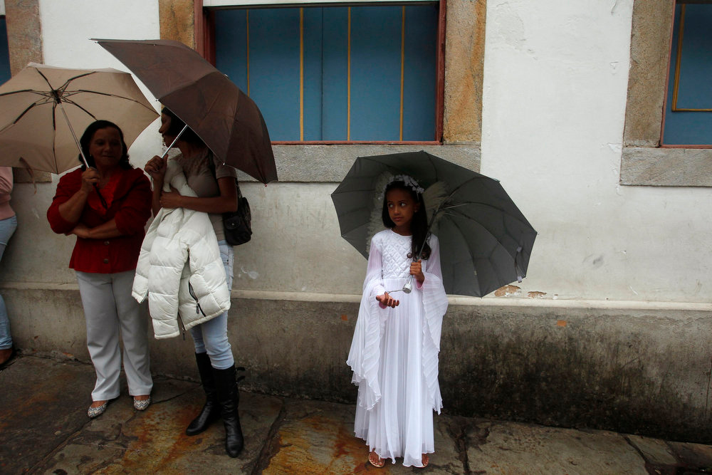 Description of . A child dressed as an angel holds an umbrella as she attends the Easter Sunday procession in the historic city of Ouro Preto in the Brazilian state of Minas Gerais, March 31, 2013. REUTERS/Pilar Olivares
