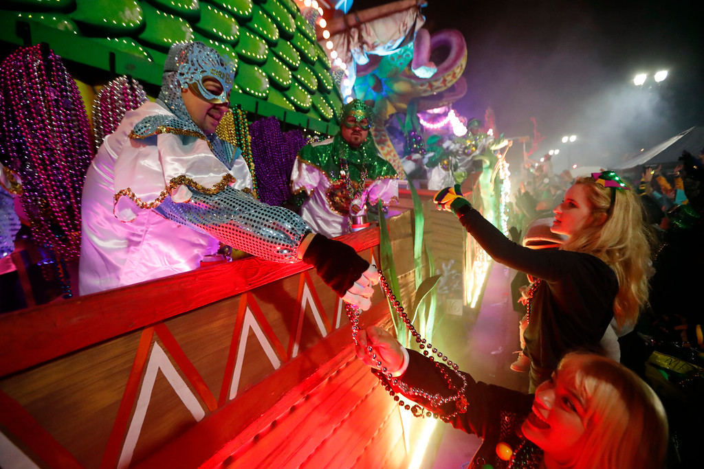 . Float riders hand beads to the crowd as the Krewe of Orpheus rolls in New Orleans, Monday, Feb. 12, 2018. Tens of thousands of revelers are expected on New Orleans streets for parades and rowdy fun as Mardi Gras caps the Carnival season in a city with a celebration of its own, its 300th anniversary. (AP Photo/Gerald Herbert)