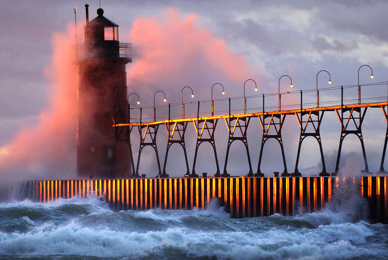 13 Nov, 2005 -  High winds spray water over the South Haven lighthouse as the warm setting sun reflects off the pier Sunday evening.  Some, standing on the beach, braved the high winds and experienced a dramatic, turbulent and colorful mid-November sunset as others watched from the comfort of their cars.