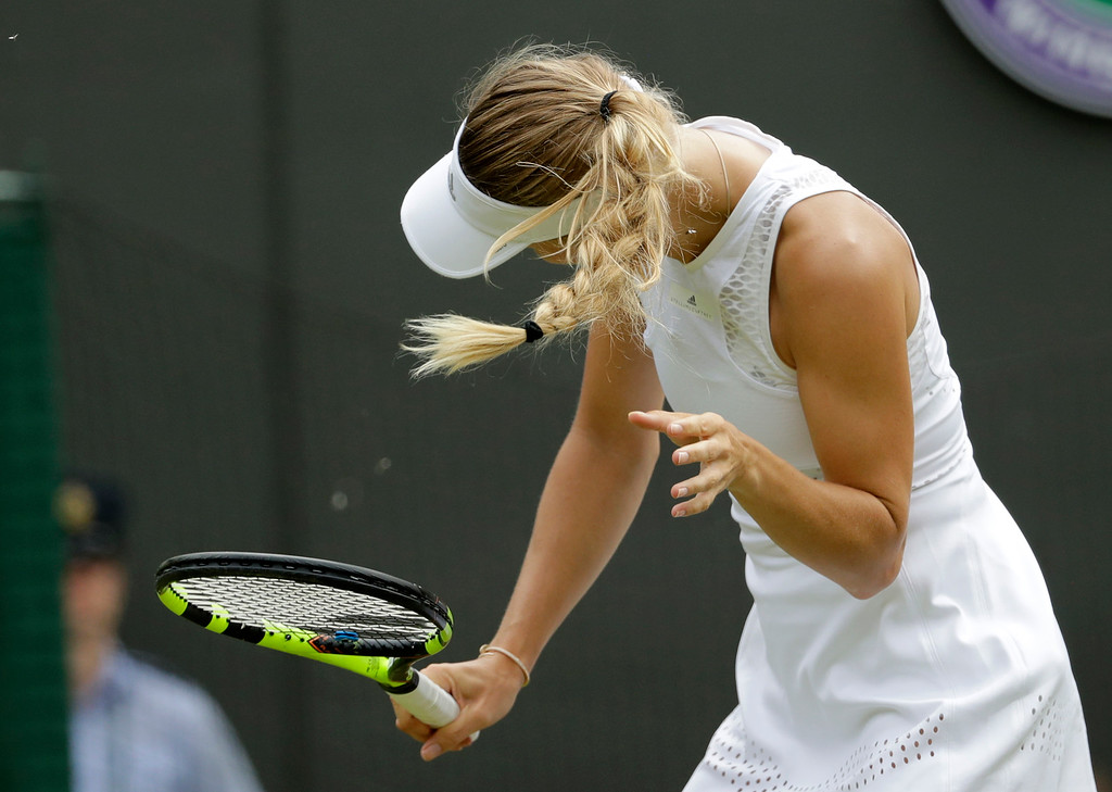 . Caroline Wozniacki of Denmark shakes her head to avoid the flying insects on court during the women\'s singles match against Ekaterina Makarova of Russia on the third day at the Wimbledon Tennis Championships in London, Wednesday July 4, 2018. (AP Photo/Ben Curtis)