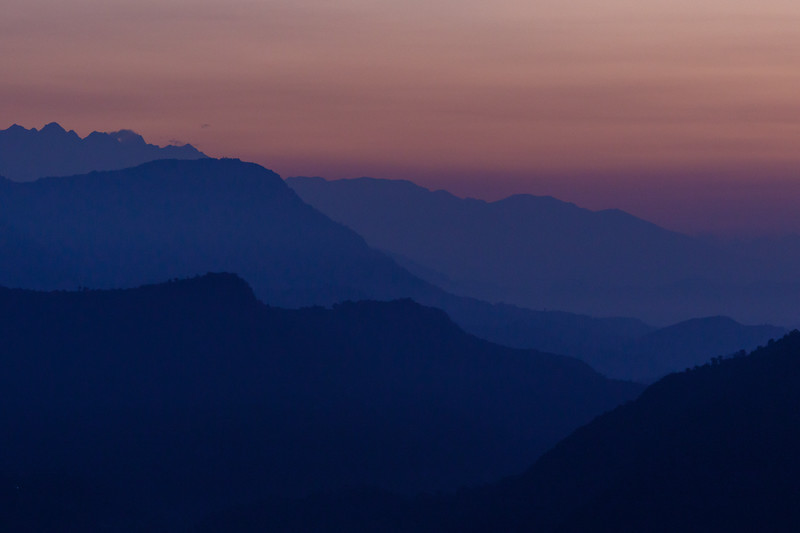 Purple and blue colors on distant silhouetted hills before sunrise - Sarangkot Road, Pokhara, Western Development Region, Nepal (NP)
