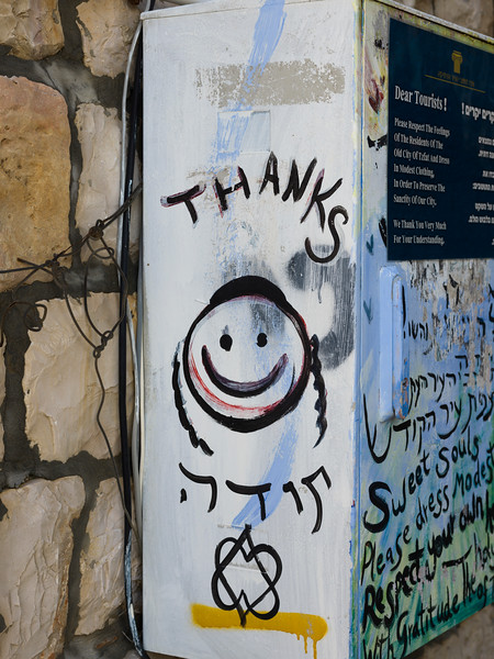 Close-up of box with graffiti and information sign on wall, Old City, Safed, Northern District, Israel