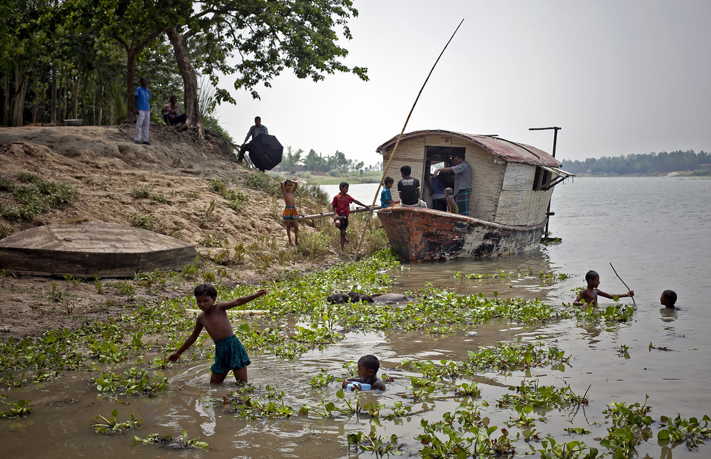 """. Kids play in a river in front of a floating health care clinic operated by Shidhulai Swanirvar Sangstha May 20, 2014 in Pabna district, Bangladesh. About 3 million people live on geographically isolated islands, known as \""""chors\"""", with no roads, no electricity, and no medical facilities. Every year, the nation is inundated with monsoonal rains which can flood up to two thirds of the country. Approximately 10 million people live in parts of Bangladesh lying less than a meter above current sea levels. (Photo by Allison Joyce/Getty Images)"""