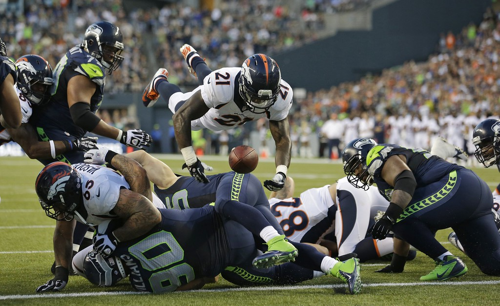 . Denver Broncos running back Ronnie Hillman (21) fumbles as he goes over the top on a play against the Seattle Seahawks in the first half of a preseason NFL football game, Saturday, Aug. 17, 2013, in Seattle. The fumble was picked up by Seahawks\' Brandon Browner, not seen, and returned for a touchdown. (AP Photo/Elaine Thompson)