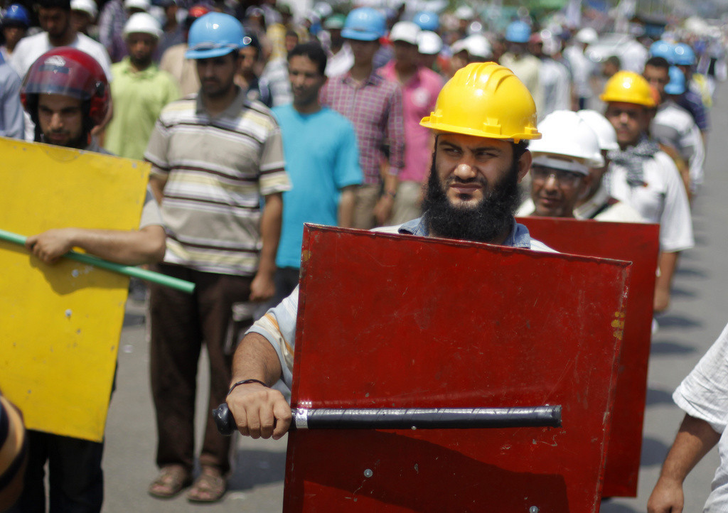 . Supporters of Egypt\'s Islamist President Mohammed Morsi hold sticks and wear protective gear during their training outside of the Rabia el-Adawiya mosque near the presidential palace, in Cairo, Egypt, Tuesday, July 2, 2013. (Associated Press: Amr Nabil)