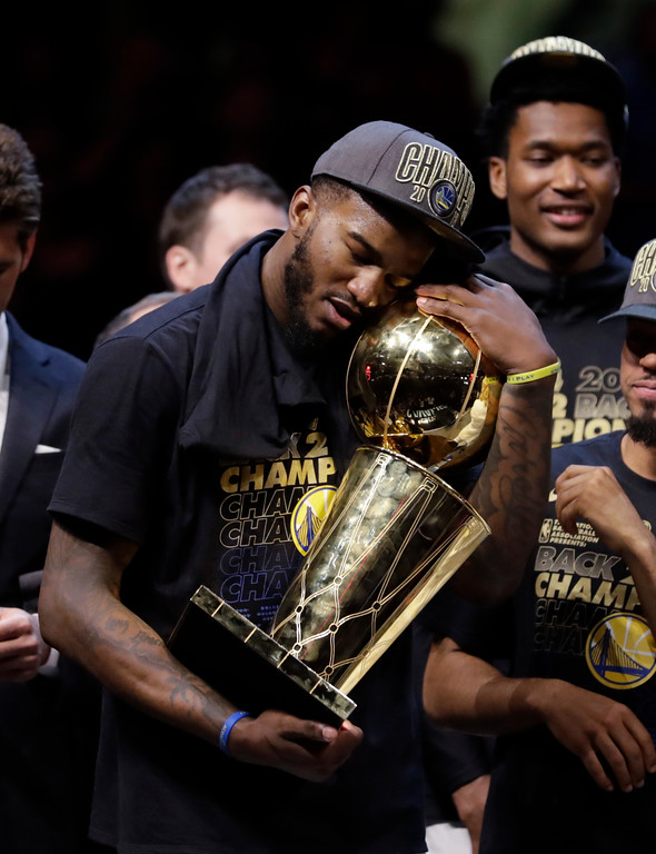 . Golden State Warriors\' Jordan Bell holds the championship trophy after the Warriors defeated the Cleveland Cavaliers 108-85 in Game 4 of basketball\'s NBA Finals to win the NBA championship, Friday, June 8, 2018, in Cleveland. (AP Photo/Tony Dejak)
