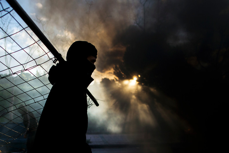 . A student carries a fence to add to a barricade, with smoke rising from a fire started,  during the first day of  a student strike to protest a government education reform and cutbacks in grants and staffing, at Complutense University in Madrid, Spain, Wednesday, March 26, 2014. Spanish police say they have arrested more than 50 students when the police moved in to end the occupation of a campus building after the university had asked them to intervene. Students, many with their faces covered, set fire to trash containers and set up barricades on at least two streets in the university complex during the protest. (AP Photo/Andres Kudacki)