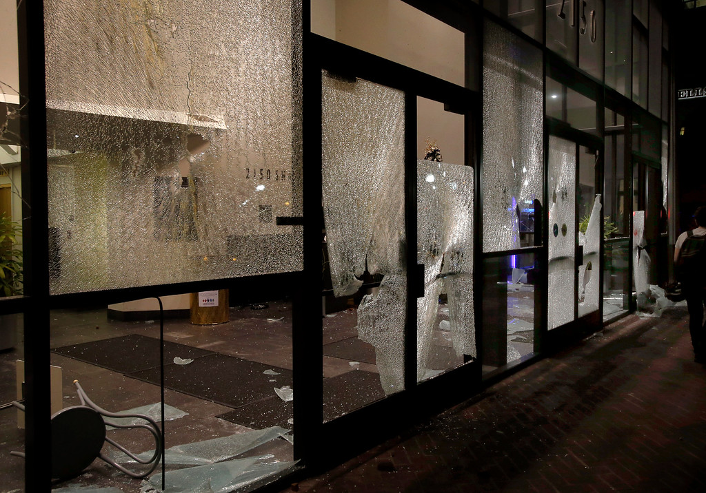 . A trail of broken glass is left by protesters along Shattuck Avenue in Berkeley, Calif., late Sunday evening, Dec. 7, 2014, during a second consecutive night of unrest in the city over the killings of two unarmed black men by police in Ferguson, Mo., and New York. (Karl Mondon/Bay Area News Group)