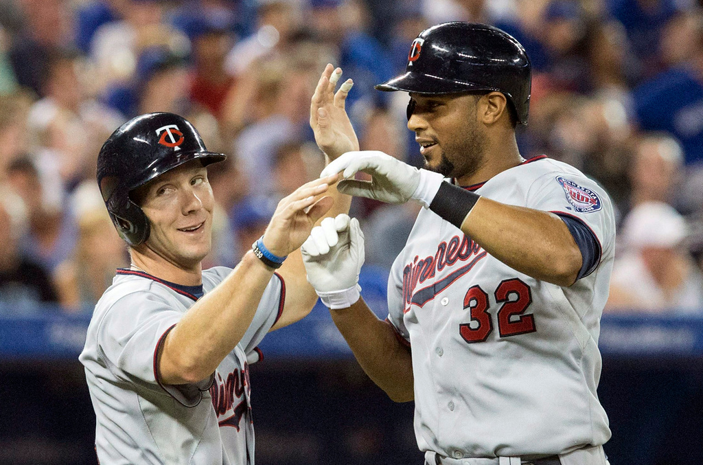 . Minnesota\'s Aaron Hicks, right, is congratulated by teammate Clete Thomas after lining a two-run home run over the right field fence off Blue Jays starter Todd Redmond during the fifth inning. (AP Photo/The Canadian Press, Chris Young)