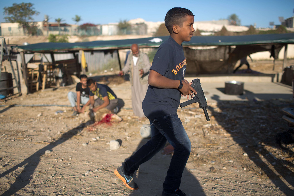 . A boy runs past members of the Bedouin Zanun family, who belong to the Azazme tribe, as they slaughter a sheep on the first day of the Muslim feast of Eid al-Adha on October 15, 2013 in their village of Wadi Naam, currently unrecognized by Israeli authorities, near the southern city of Beersheva in the Israeli Negev desert. AFP PHOTO/MENAHEM KAHANA/AFP/Getty Images