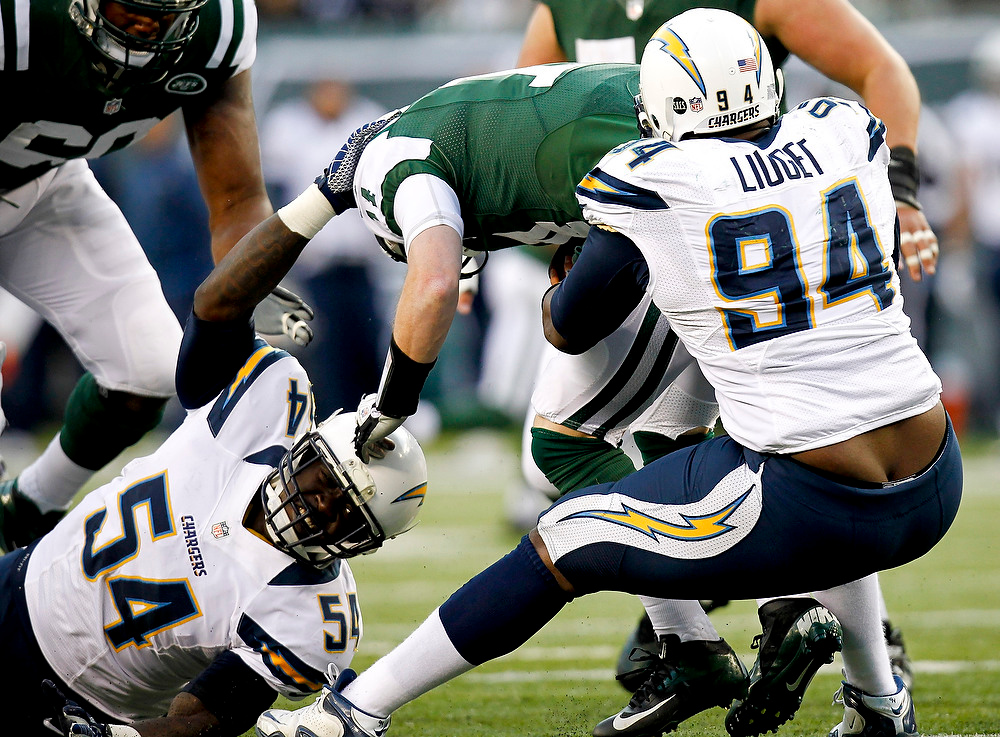 Description of . Corey Liuget #94 and Melvin Ingram #54 of the San Diego Chargers sack Greg McElroy #14 of the New York Jets at MetLife Stadium on December 23, 2012 in East Rutherford, New Jersey. (Photo by Jeff Zelevansky /Getty Images)