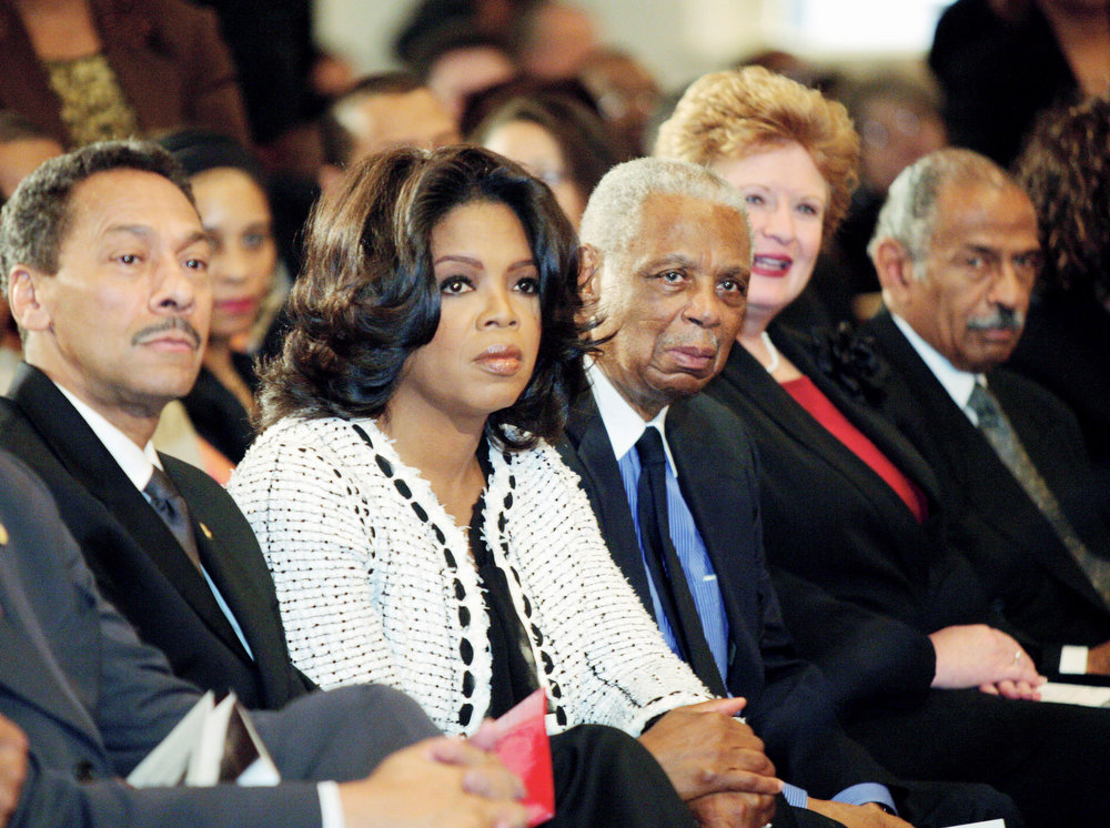 Description of . Television talk show host Oprah Winfrey, second left, listens to speeches, during a memorial services for Rosa Parks at the Metropolitan AME Church in Washington, Monday, Oct. 31, 2005. From left are, Rep. Melvin Watt, D-N.C., Winfrey, U.S. Court of Appeals Judge Damon Keith, Sen. Debbie Stabenow, D-Mich., and Rep. John Conyers, D-Mich.    (AP Photo/Ron Thomas)