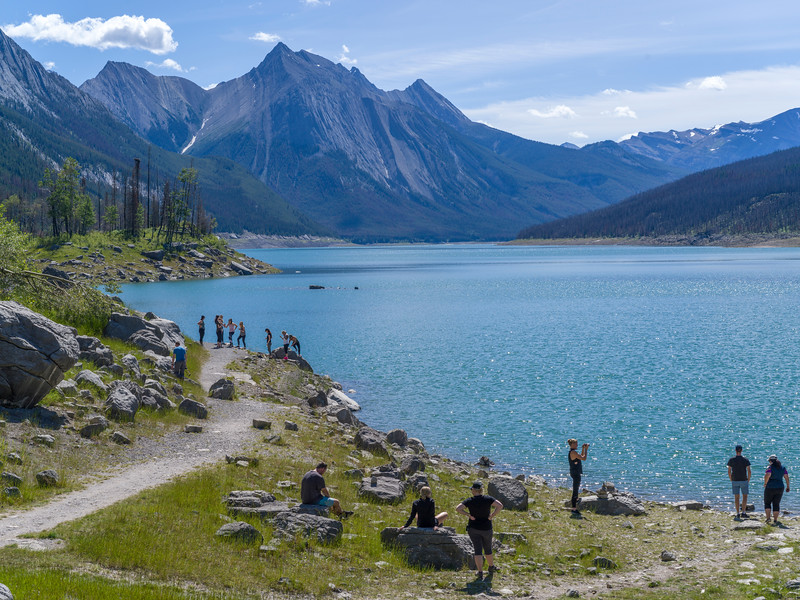 Tourists at lakeside, Medicine Lake, Maligne Lake Road, Jasper National Park, Jasper, Alberta, Canada