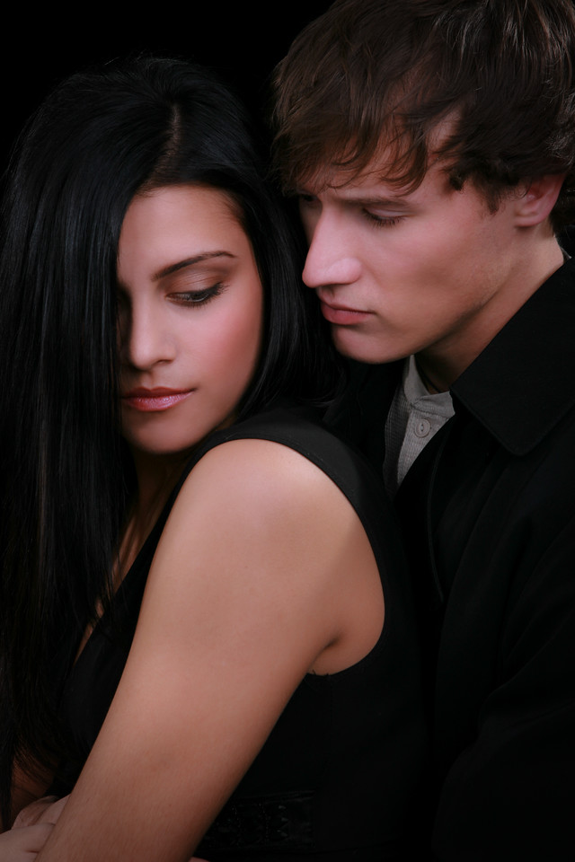 Young Couple Holding together Low Key Portrait on Dark Background